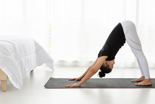 Asian women doing yoga exercise at home, stretching in downward facing dog  pose or adho mukha svanasana in white bedroom.   Premium Photo