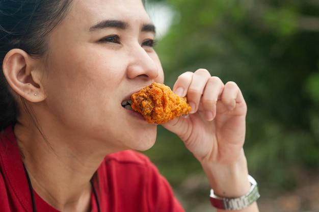 테이블에 앉아 닭 날개를 먹는 아시아 여성 프리미엄 사진