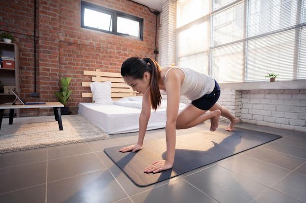 アジアの女性は「マウンテンクライマー」と呼ばれる自宅で屋内で運動します。 無料写真