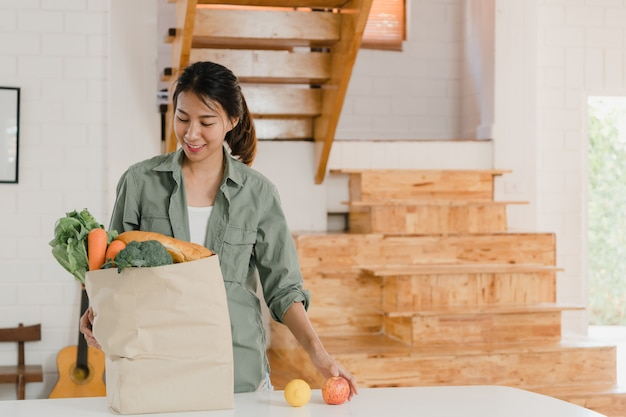 Asian women holding grocery shopping paper bags at home Free Photo