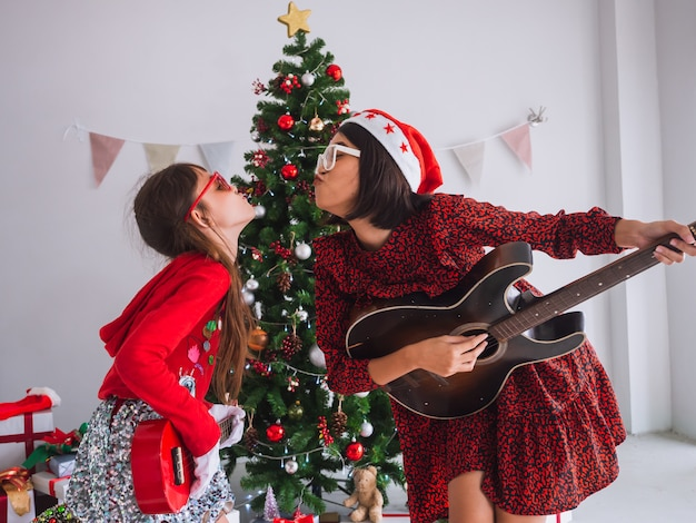 Asian women and kid celebrate christmas by struming the guitar in house Premium Photo