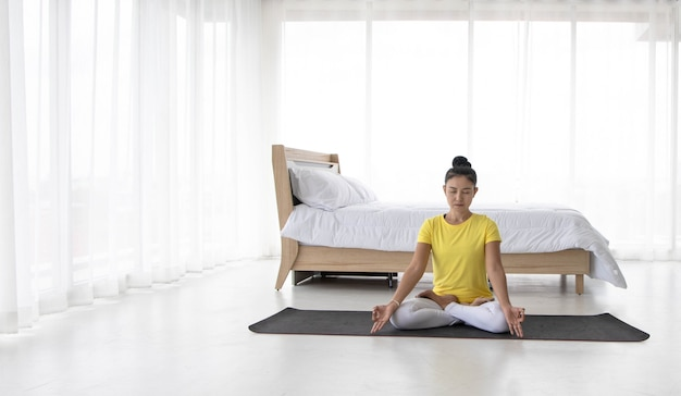 Asian women meditate while practicing yoga Premium Photo