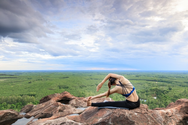 Asian women play it yoga on the mountain rock cliff. Premium Photo