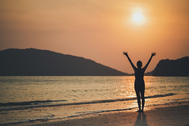 Asian women play yoga on a sand beach by the sea and mountain in the sunrise morning. exercise and meditation concept. Premium Photo