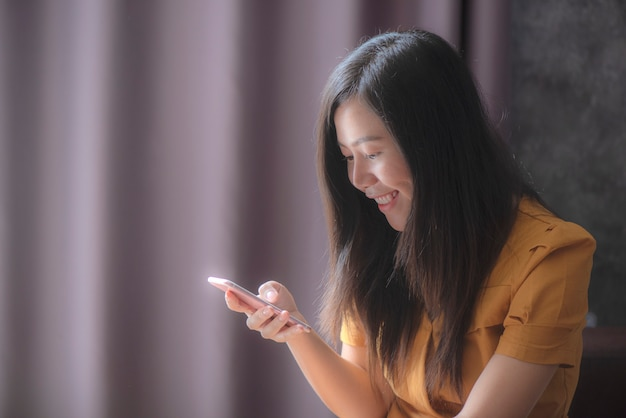 Asian women playing indoor mobile games smile happily Premium Photo
