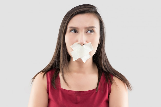 Asian women in red dresses use masking tape to close the mouth Premium Photo