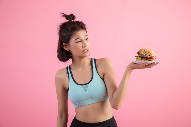Asian women refuse fast food because of slimming on pink Free Photo