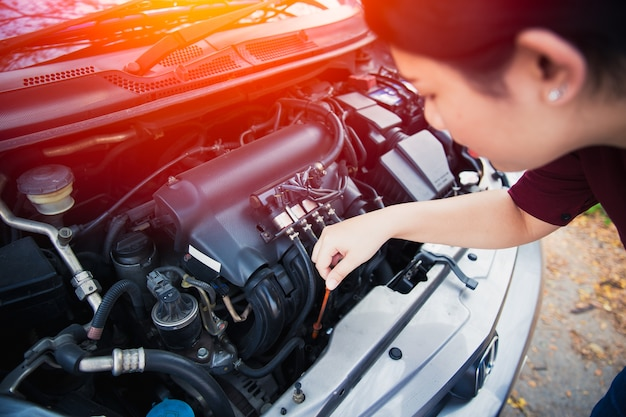 Asian women self car engine oil level check up before go trip ...