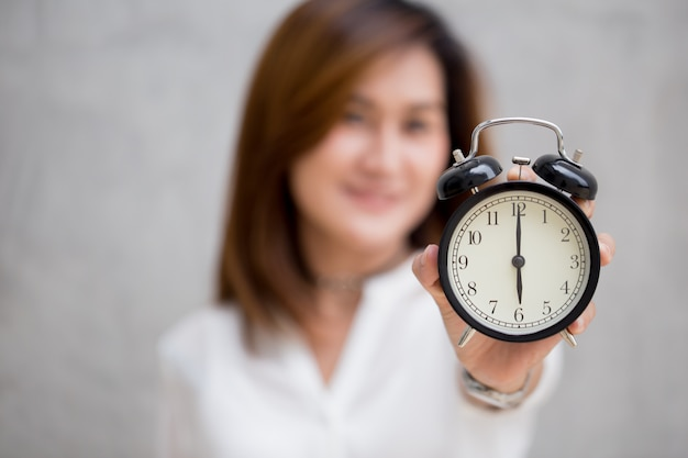 Asian women show clock times at 6 o'clock, it's time to do something concept Premium Photo