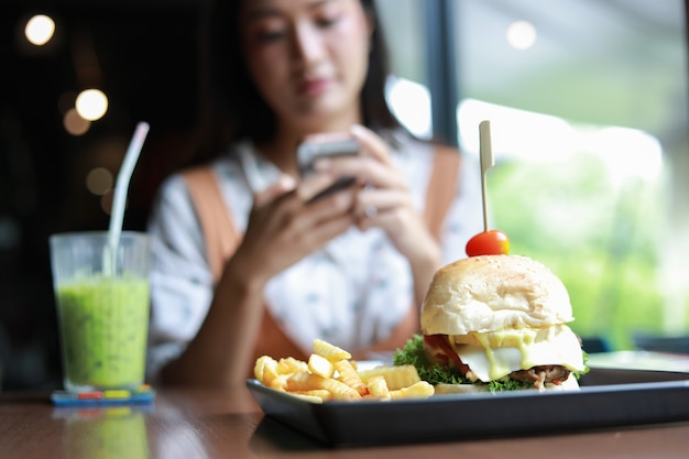 Asian women smiling and happy and enjoyed eating hamburgers at coffee and restaurant on relax time Premium Photo