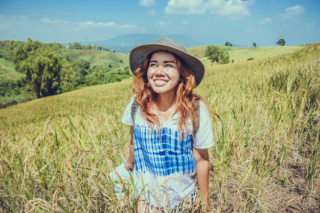 Asian women travel relax in the holiday. expand survey map mountain field. crop rices ranch on hill. Premium Photo