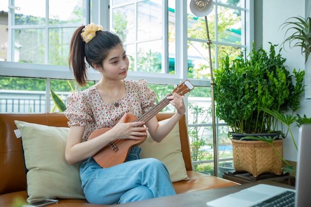 Азиатские женщины используют свои портативные компьютеры, чтобы учиться и практиковаться в игре на укулеле в интернете дома. Premium Фотографии