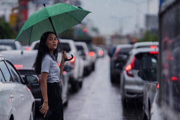Le donne asiatiche usano l'ombrello mentre attraversano la strada mentre piove Foto Gratuite
