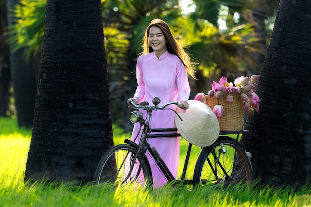 Asian women vietnam is girl trolley bike to the store after the lotus flower basket. Premium Photo