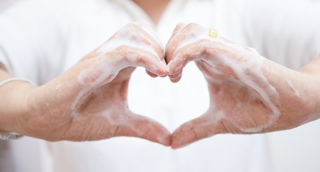 アジアの女性は石鹸で手を洗ったりきれいにしたりして、手札を作り、covid-19の発生中に励ましを送ります。 Premium写真