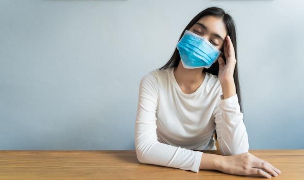 아시아 여성들은 두통 때문에 마스크를 쓰고 머리를 잡고있다. 그녀는 스트레스로 인해 열이 나 편두통을 앓고있다. | 프리미엄 사진
