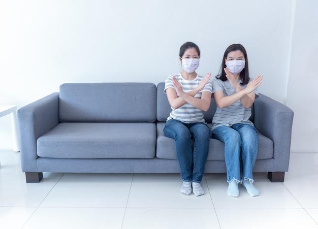 Азиатские женщины в масках сидят вместе на диване без места и пересекают знак социального дистанцирования, чтобы уменьшить распространение коронавируса Premium Фотографии