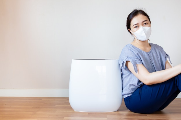 Asian women who has a health problem from air pollution in her house sitting beside the air purifier machine in the living room on the wooden floor Premium Photo