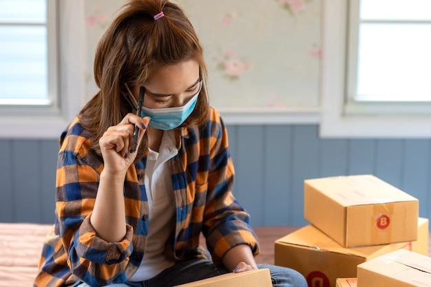 Азиатская работа женщин сидит и думает о маркетинговом анализе от дома в поле комнаты с почтовой посылкой, продавая онлайн концепция идей, новое нормальное. Premium Фотографии