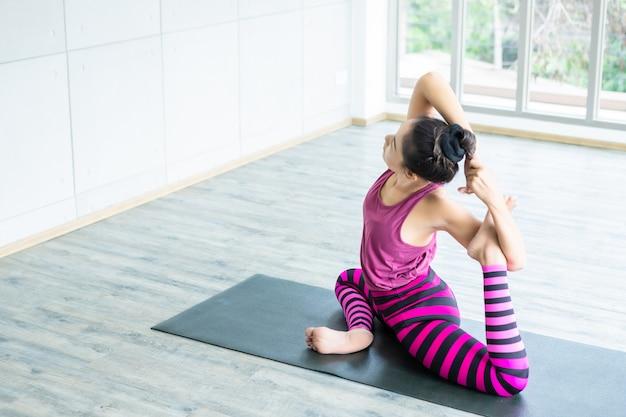 Тренировка йоги азиатских женщин практикуя тренировку надевала розовые одежды и практикует образ жизни и здоровье пригодности раздумья и фитнес пригодности в спортзале Premium Фотографии