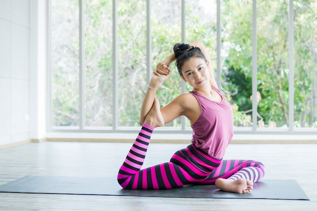 Asian women workout practicing yoga training put on pink clothes and practice meditation wellness lifestyle and health fitness concept in a gym Premium Photo