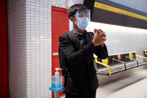 Asian working men wash hands with alcohol gel into subway Premium Photo