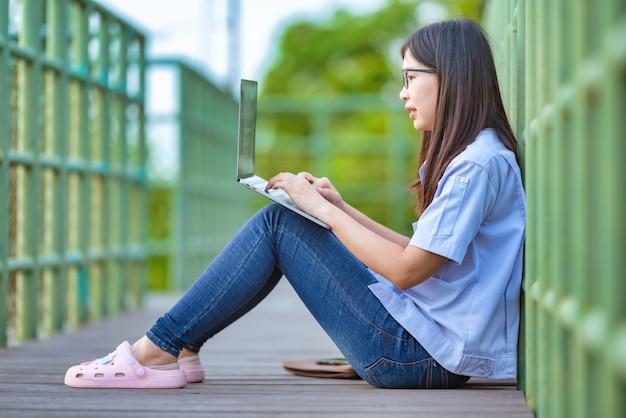 Asian working woman in public park using laptop Premium Photo