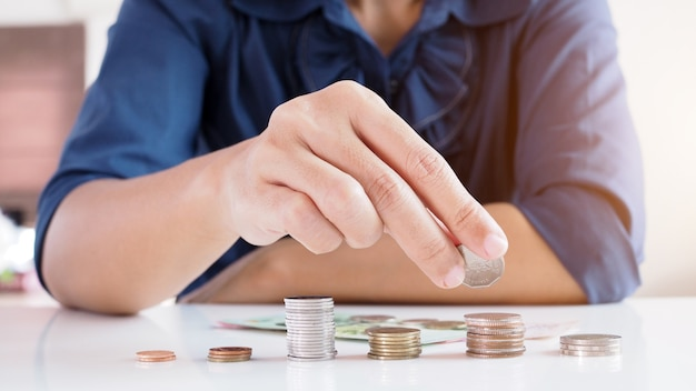 Asian working women counting coins and saving money for financial planning. Premium Photo