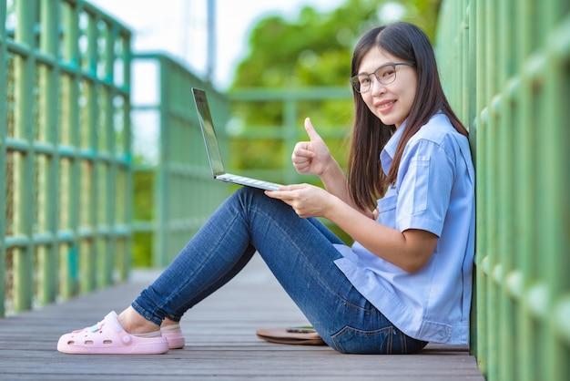 Asian working women in public park using laptop modern lifestyle Premium Photo