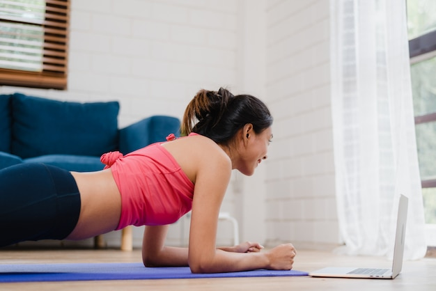 Asian yoga trainer woman using laptop for live teaching how to do yoga in living room at home. Free Photo