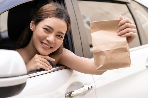 Азиатский молодой взрослый в машине держит одноразовую сумку для еды на вынос из ресторана обслуживания проезда. drive thru - это новая нормальная и популярная услуга после пандемии коронавируса covid-19. Premium Фотографии