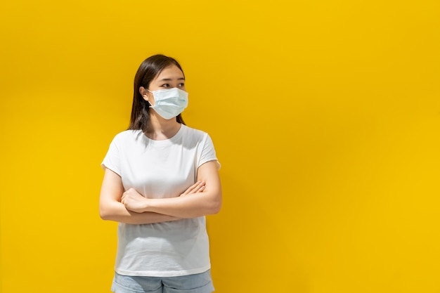 Asian young attractive woman wearing a protective hygiene mask over her face to protect flu and virus. unwell influenza in infected woman portrait with yellow background. covid19 and coronavirus. Premium Photo