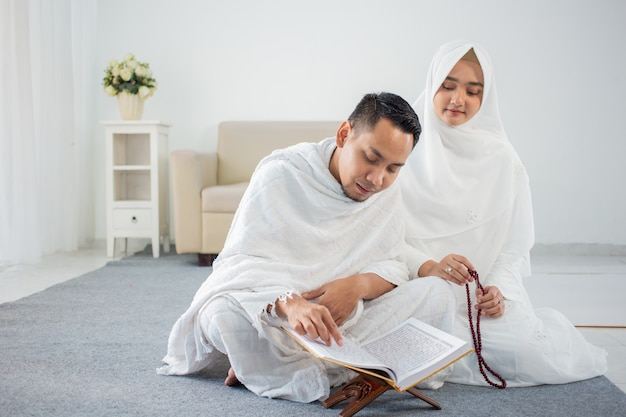 アルコーランと数珠で祈るアジアの若いカップル Premium写真