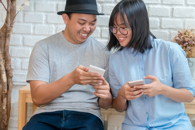 Asian young couple talking and using the smart mobile phone with happiness action Premium Photo