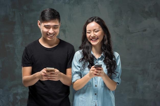 Giovani coppie asiatiche facendo uso del cellulare, ritratto del primo piano. Foto Gratuite