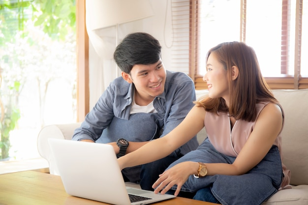 Asian young couple using laptop computer think and searching internet together Premium Photo