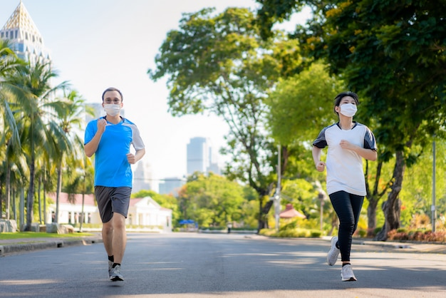 Asian young couple woman and man are jogging and exciseing outdoor ...