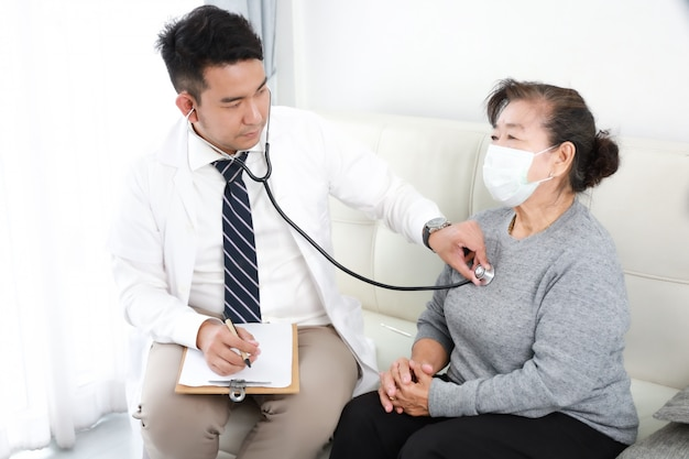 Asian young doctor talking with senior woman in hospital Premium Photo