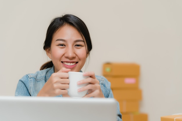 Asian young entrepreneur business woman owner of sme online checking product on stock save to computer and drinking coffee working at home. Free Photo