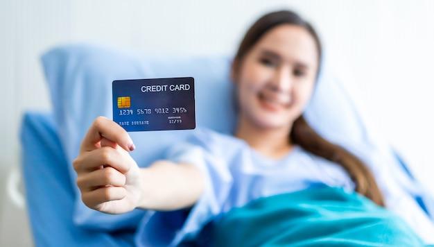 아시아 젊은 여성 환자 웃는 얼굴 추상 흐림 방 병원 배경에 침대에 누워 신용 카드를 들고 쇼에 초점 프리미엄 사진