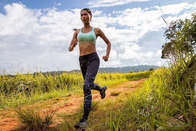 Asian young fitness woman exercise running at forest trail. Premium Photo