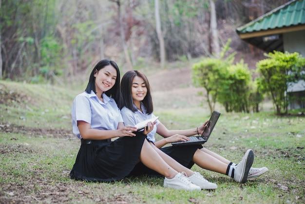 Азиатская маленькая девочка в школьной форме использует компьтер-книжку для образования и связи на сельской местности таиланда. Premium Фотографии