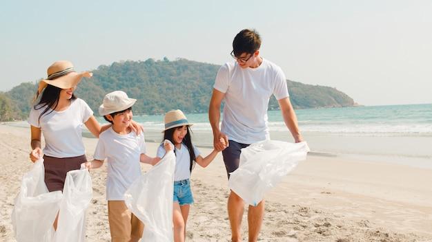 Азиатские молодые счастливые активисты семьи собирая пластичные отходы и гуляя на пляж. волонтеры азии помогают природе убирать мусор. понятие о проблемах загрязнения окружающей среды. Бесплатные Фотографии
