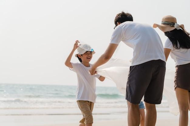 Азиатские молодые счастливые активисты семьи собирая пластичные отходы на пляже. волонтеры азии помогают содержать природу в чистоте и собирать мусор. понятие о проблемах загрязнения окружающей среды. Бесплатные Фотографии