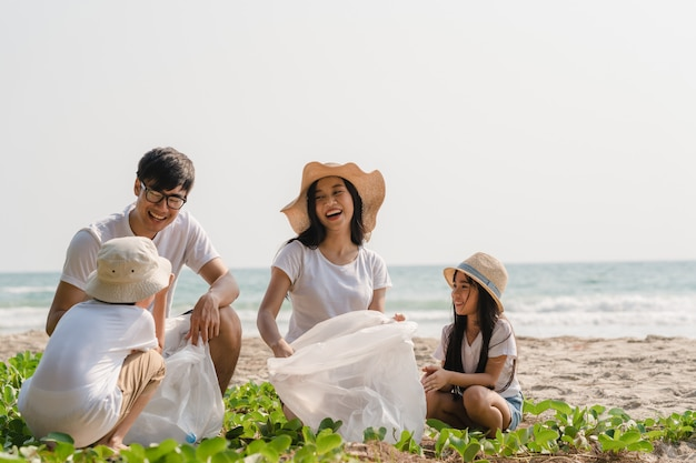 해변에서 플라스틱 폐기물을 수집하는 아시아 젊은 행복한 가족 운동가. 아시아 자원 봉사자들은 자연을 깨끗하게 유지하고 쓰레기를 줍도록 도와줍니다. 환경 보전 오염 문제에 대한 개념. 무료 사진