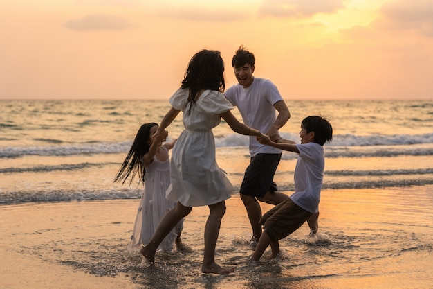 Asian young happy family enjoy vacation on beach in the evening. dad, mom and kid relax playing together near sea when silhouette sunset. lifestyle travel holiday vacation summer concept. Free Photo