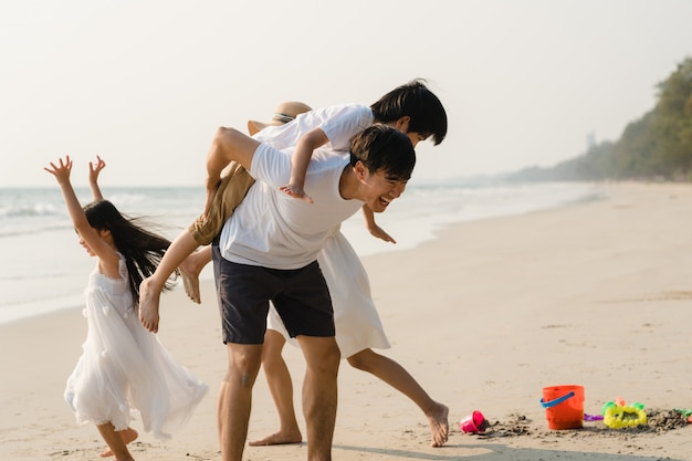 Asian young happy family enjoy vacation on beach in the evening. dad, mom and kid relax playing together near sea when sunset while travel holiday. lifestyle travel holiday vacation summer concept. Free Photo