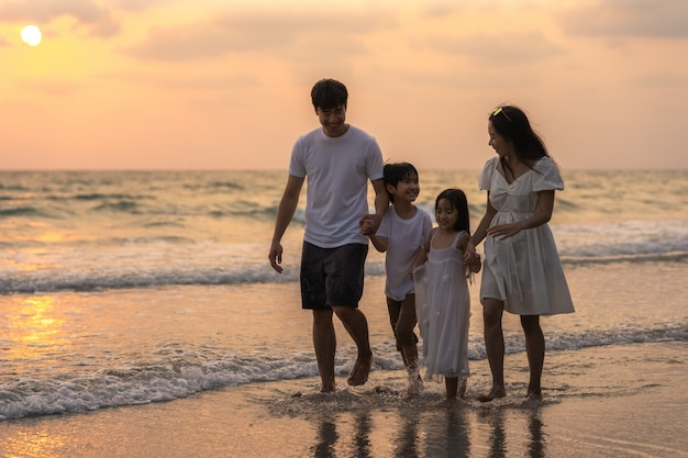 Asian young happy family enjoy vacation on beach in evening. dad, mom and kid relax walking together near sea when sunset while travel holiday trip. lifestyle travel holiday vacation summer concept. Free Photo