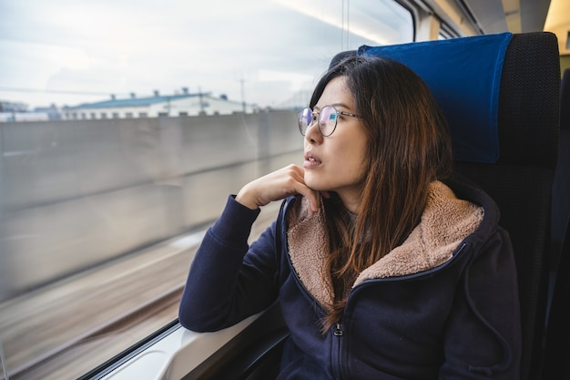Asian young lady passenger sitting in a depressed mood beside the window inside train which travel Premium Photo