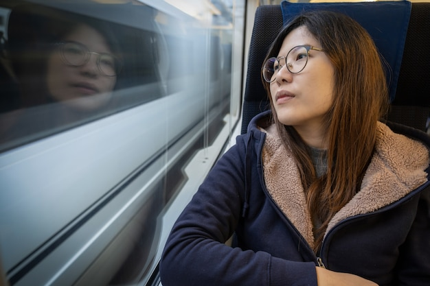 Asian young lady passenger sitting in a depressed mood beside the window inside train Premium Photo
